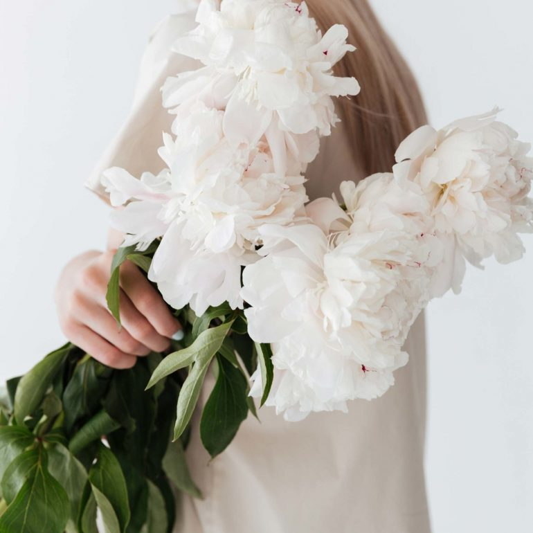 blonde-woman-standing-isolated-holding-flowers-P8B3XEP-1-scaled.jpg